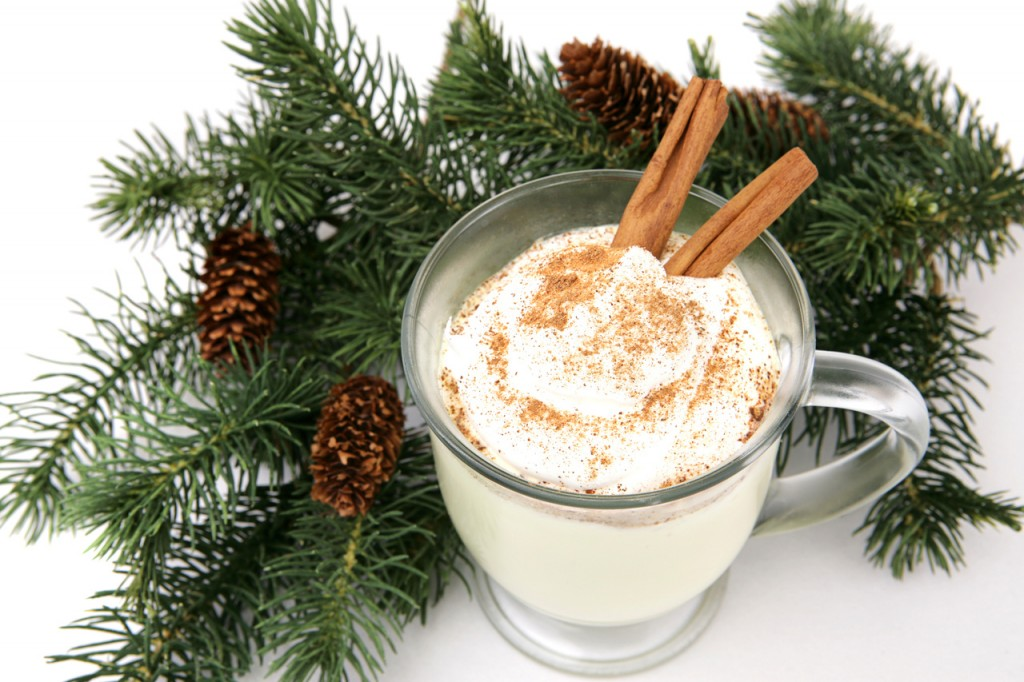 A mug of eggnog garnished with whipped cream, nutmeg and cinnamon sticks, nestled in pine branches. White background.